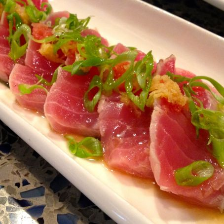 On a shallow plate, mix together the ginger, sesame seeds, and cracked black pepper. Season the tuna with salt. Make 1/2-inch deep slices in the tuna, every 1/4- to 1/2-inch or so to make it.